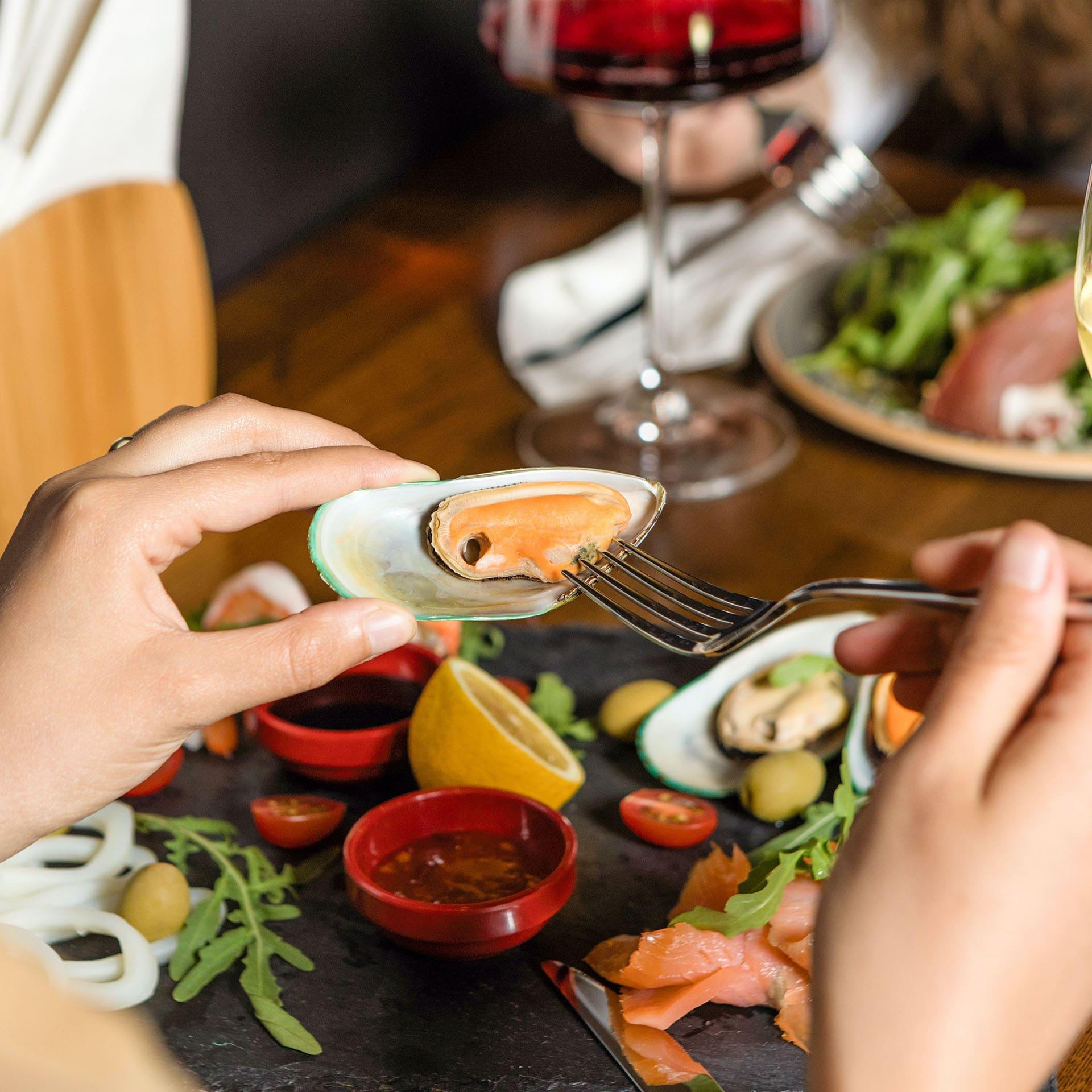 manos sosteniendo un mejillón con salsa de tomate en un cuenco en la mesa